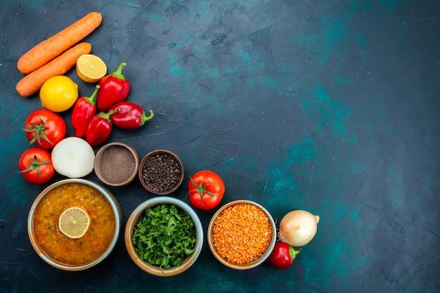 Draufsicht der gemüsesuppe mit frischem gemüsegrün und gewürzen auf dunkelblauer oberfläche