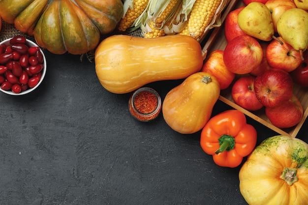Draufsicht der gemüsezusammensetzung mit kürbissen und äpfeln auf schwarzem hintergrund