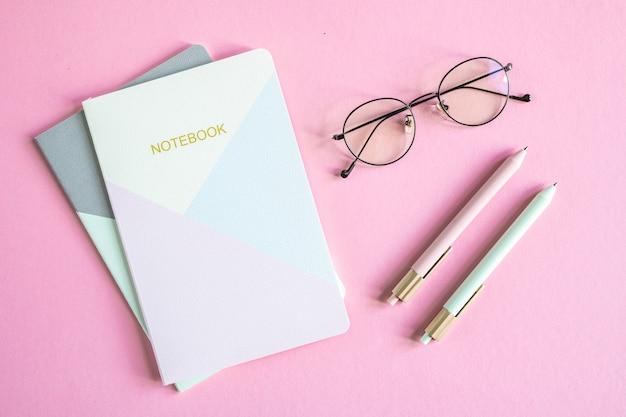 Draufsicht der geschäftspersonbrillen, zwei notizbücher und stifte über rosa hintergrund