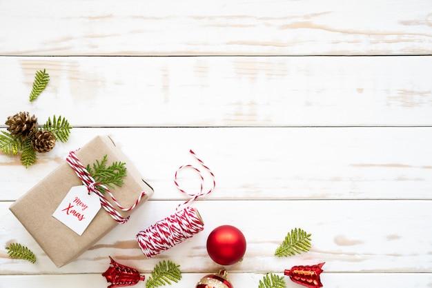 Draufsicht der geschenkbox, der kiefernkegel, des roten sternes und der glocke auf einem hölzernen weißen hintergrund.