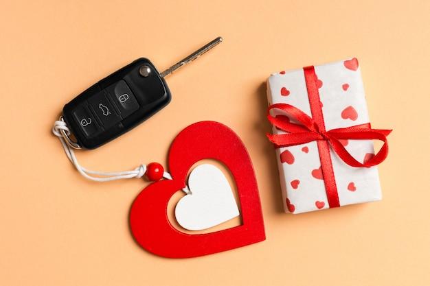 Draufsicht der geschenkbox, des autoschlüssels und des hölzernen herzens auf tabelle.