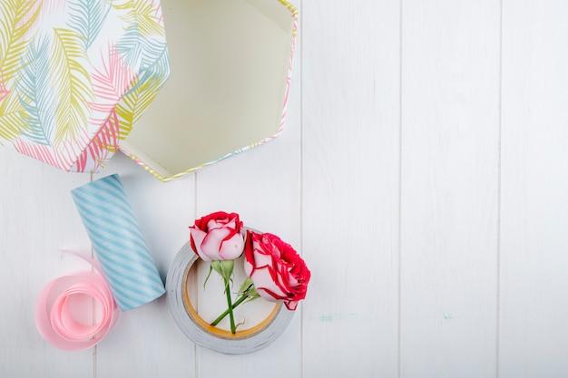 Draufsicht der geschenkbox und der roten farbrosen mit rollen des klebebandes auf weißem hölzernem hintergrund mit kopienraum