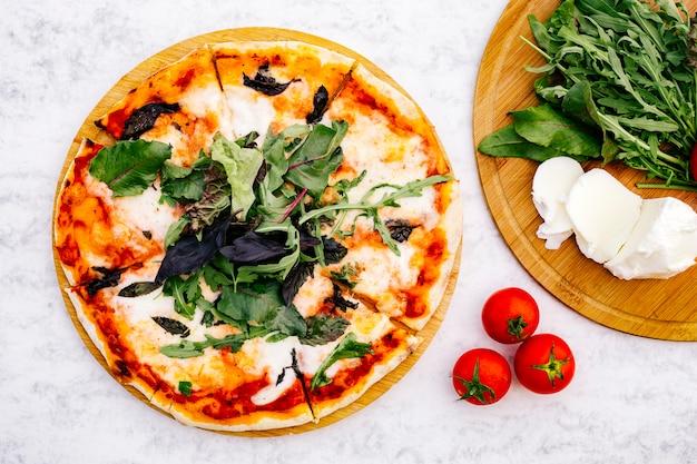 Draufsicht der geschnittenen margherita-pizza, die mit rucola gekrönt wird