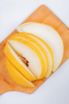 Draufsicht der geschnittenen melone auf schneidebrett auf weißem hintergrund