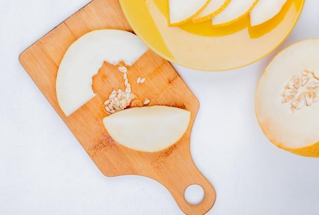 Draufsicht der geschnittenen melone und der samen auf schneidebrett und in platte mit geschnittenem auf weißem hintergrund
