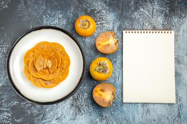 Draufsicht der geschnittenen persimone auf pfannkuchen auf heller oberfläche