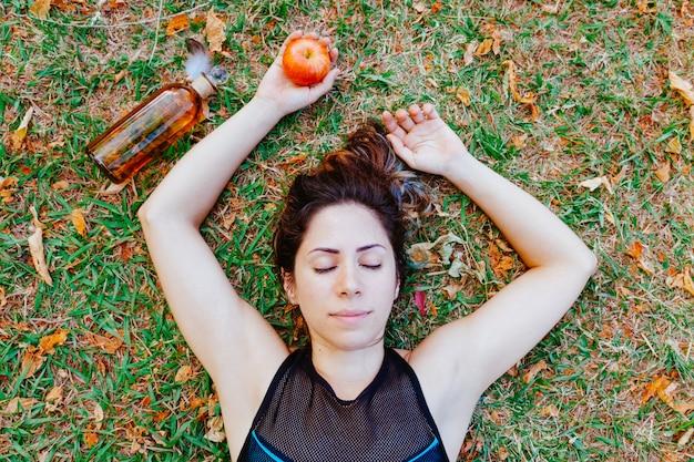 Draufsicht der gesunden frau, die auf dem schlafenden gras liegt. junge frau, die einen apfel hält, der sich um ihre gesundheit kümmert. gesunder lebensstil für menschen im sommer. iss jeden tag einen apfel für eine ausgewogene ernährung.