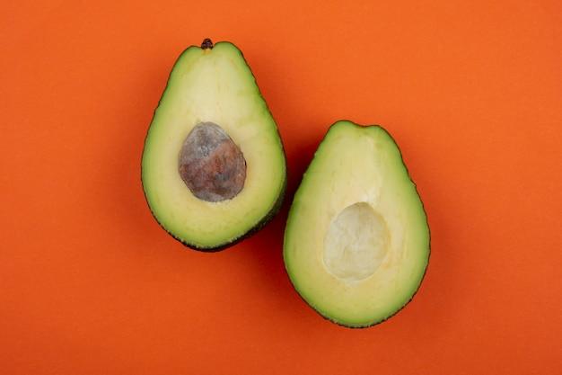 Draufsicht der gesunden frischen köstlichen avocado auf orange oberfläche