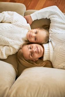 Draufsicht der glücklichen familie, die zu hause entspannt. vertikale aufnahme der schönen jungen mutter und ihrer niedlichen tochter, die kopf an kopf nebeneinander auf dem sofa liegen, glücklich lächeln und pullover tragen