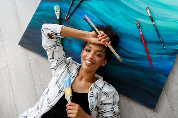 Draufsicht der glücklichen malerin africana amerikanerin, die auf leinwand liegt und die kamera mit pinseln in den händen betrachtet.