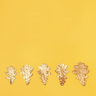 Draufsicht der goldenen gemalten blätter von eichen auf gelbem hintergrund. herbstliche grußkarte. von oben betrachten.