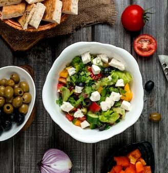 Draufsicht der griechischen salatschüssel mit weißkäse-paprika-gurke und tomate