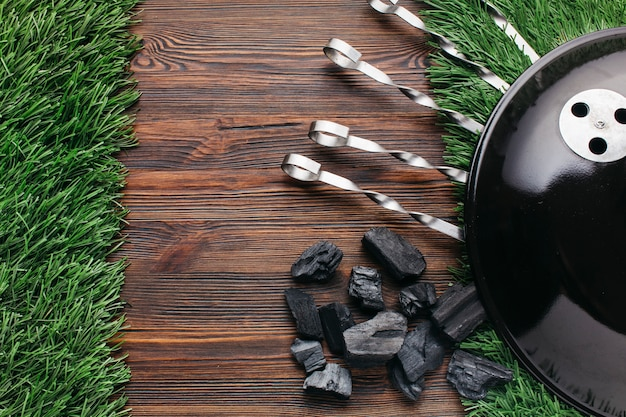 Draufsicht der grillaufsteckspindel und der kohle auf grasmatte