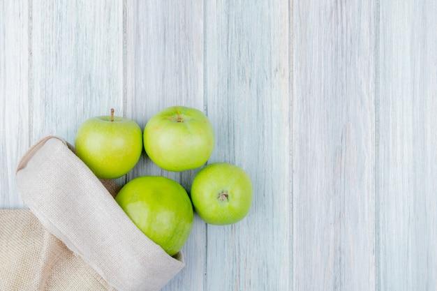 Draufsicht der grünen äpfel, die aus sack auf hölzernem hintergrund mit kopienraum verschütten