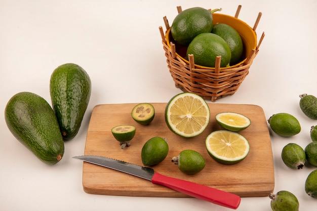 Draufsicht der grünen kalkscheiben auf einem hölzernen küchenbrett mit messer mit limetten auf einem eimer mit feijoas und avocados lokalisiert auf einer weißen wand
