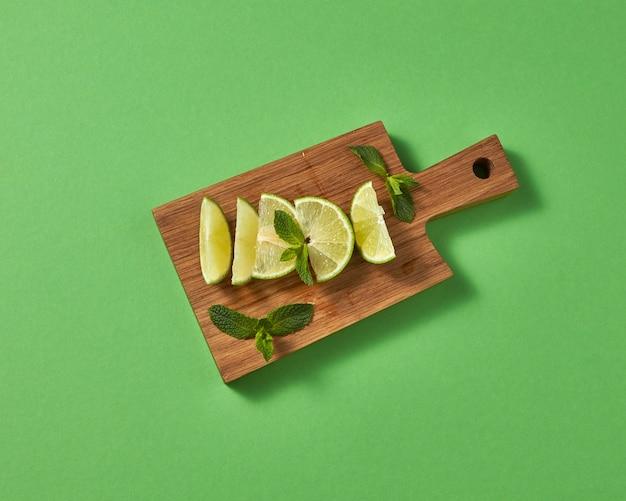 Draufsicht der grünen limette der zitrusfrüchte mit zweigen der grünen minze auf braunem brett auf einer grünen wand. konzept von kalten alkoholischen oder alkoholfreien sommergetränken.