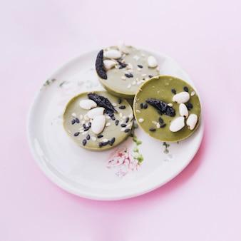 Draufsicht der grünen runden schokolade mit erdnuss- und sesamsamenbelag