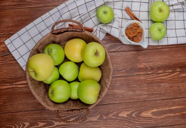 Draufsicht der grünen und gelben äpfel im korb mit apfelmarmelade und zimt auf kariertem stoff und hölzernem hintergrund