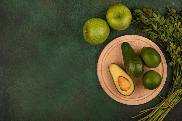 Draufsicht der grünhäutigen avocados auf einem hölzernen küchenbrett mit limetten mit grünen äpfeln und petersilie lokalisiert auf einer grünen oberfläche mit kopierraum