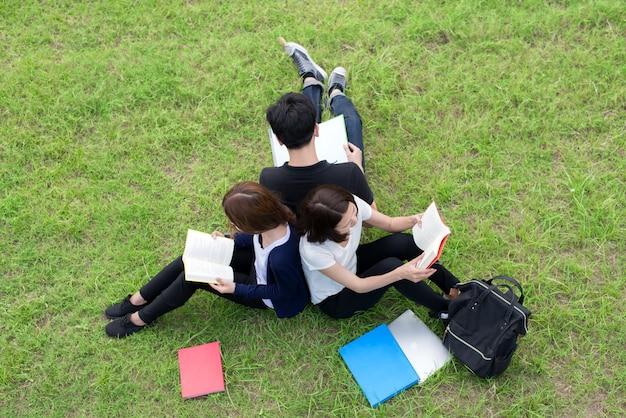 Draufsicht der gruppe asiatischer studenten, die zusammen am park sitzen.
