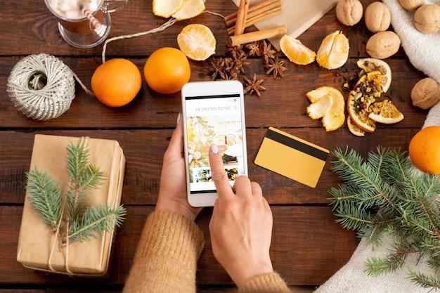 Draufsicht der hände der frau, die startknopf auf smartphone-anzeige berührt, um online-shop zu betreten