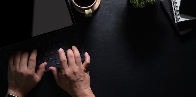 Draufsicht der hände des mannes, die auf laptop schreiben