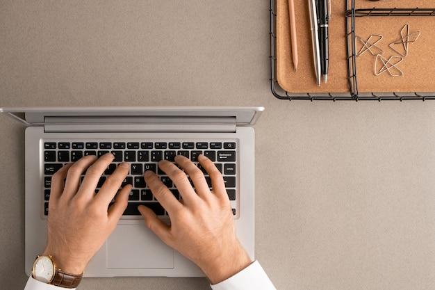 Draufsicht der hände des zeitgenössischen eleganten managers oder des büroangestellten, die knöpfe der laptop-tastatur drücken, während sie im netz durch schreibtisch brüten