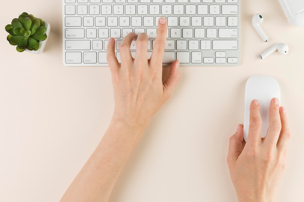 Draufsicht der hände, die auf tastatur und maus auf schreibtisch schreiben