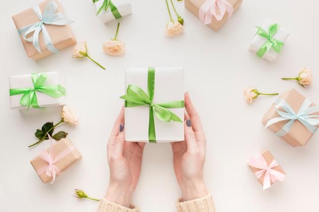 Draufsicht der hände, die geschenk mit blumen halten