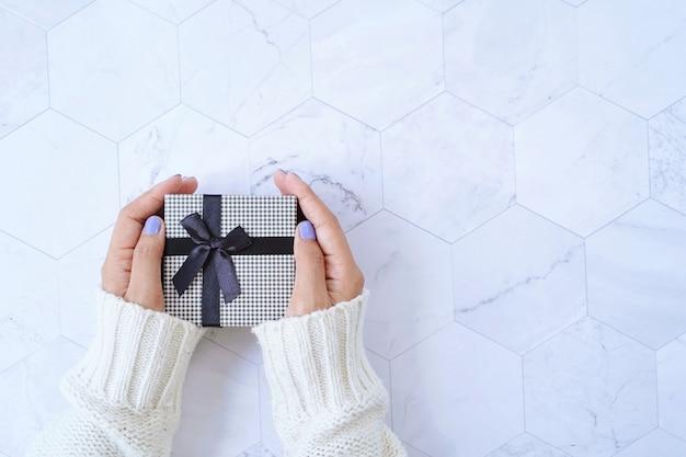 Draufsicht der hände, die geschenkbox von neujahrsfeier oder weihnachtsgeschenk auf weißem marmorhintergrund, feiertagskonzept halten
