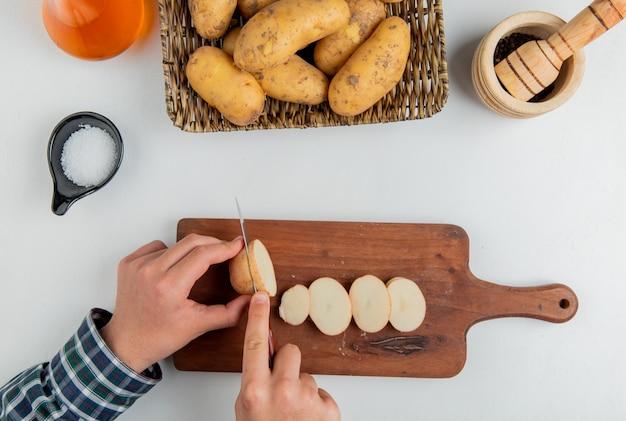 Draufsicht der hände, die kartoffel mit messer auf schneidebrett und andere in tellerbuttersalz schwarzer pfeffer auf weiß schneiden