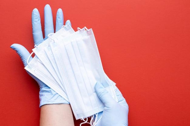 Draufsicht der hände, die medizinische masken halten
