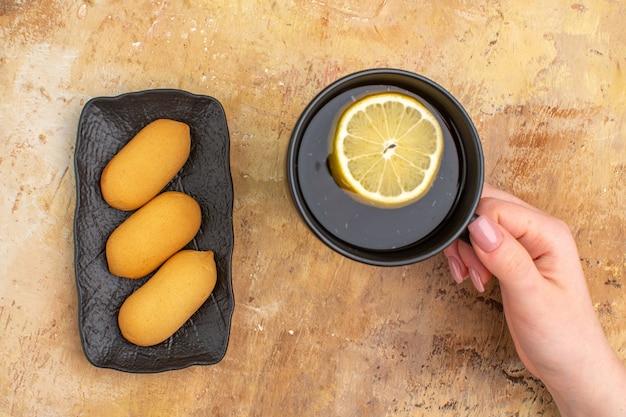 Draufsicht der hände, die schwarzen tee in einer tasse mit zitrone und keksen auf gemischtem farbhintergrund halten