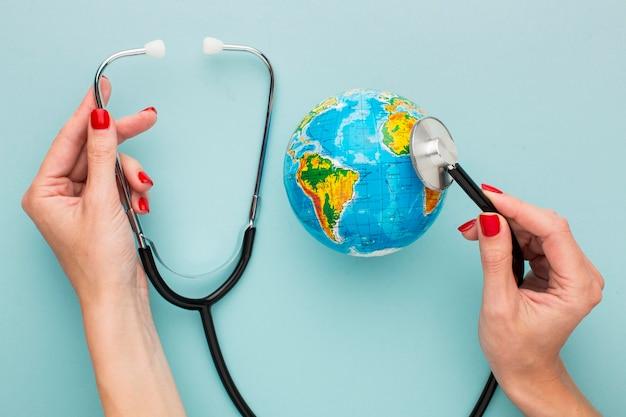 Draufsicht der hände, die stethoskop mit globus halten