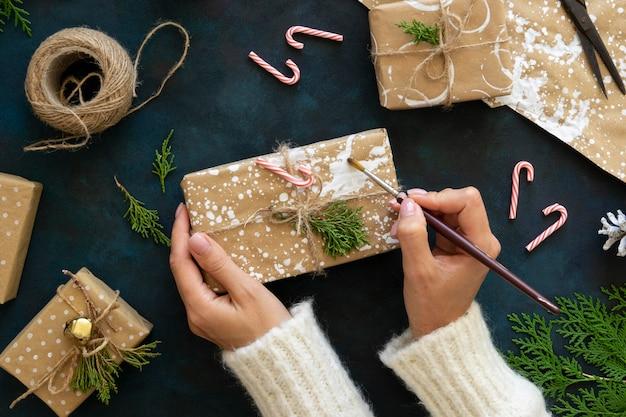 Draufsicht der hände, die weihnachtsgeschenk mit farbe verzieren