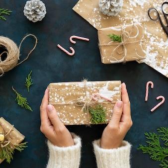 Draufsicht der hände, die weihnachtsgeschenk mit gemaltem geschenkpapier halten