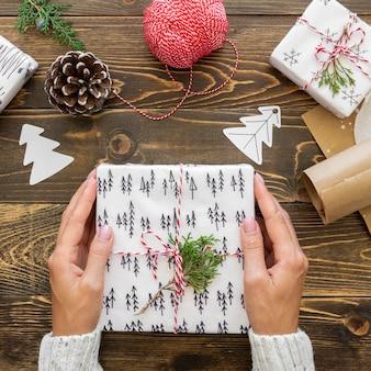 Draufsicht der hände, die weihnachtsgeschenk mit tannenzapfen und schnur halten