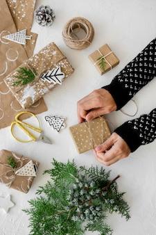 Draufsicht der hände, die weihnachtsgeschenke vorbereiten