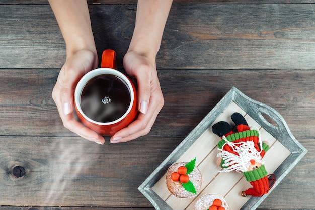 Draufsicht der hände einer frau, die warme tasse kaffee über holztisch mit weihnachtsdekoration halten