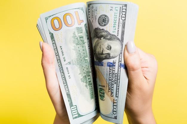 Draufsicht der hände einer geschäftsfrau, die hundert dollar-banknoten auf bunt zählen. nahaufnahme des erfolgs- und wohlstandskonzepts