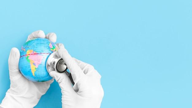 Draufsicht der hände mit chirurgischen globen, die globus mit stethoskop beraten