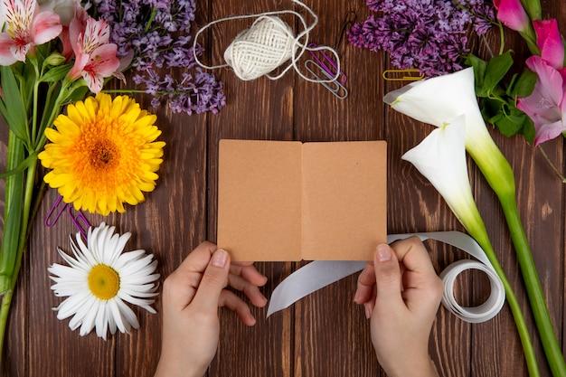 Draufsicht der hände mit einer postkarte und verschiedenen frühlingsblumen-gerbera-gänseblümchen-alstroemeria und fliederblumen auf hölzernem hintergrund
