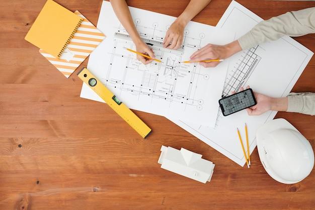 Draufsicht der hände von zwei architekten, die auf blaupause zeigen, während diskussionskizze des neuen bauprojekts beim arbeitstreffen durch holztisch diskutieren