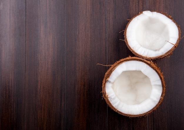 Draufsicht der halbbraunen frischen kokosnuss auf einer holzoberfläche