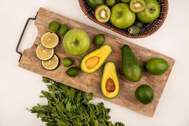 Draufsicht der halben avocado lokalisiert auf einem hölzernen küchenbrett mit limetten und feijoas mit einem eimer kiwis und äpfeln auf einer weißen oberfläche