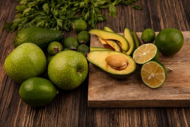 Draufsicht der halben avocado mit scheiben auf einem hölzernen küchenbrett mit äpfeln feijoas kalk und petersilie lokalisiert auf einer hölzernen oberfläche