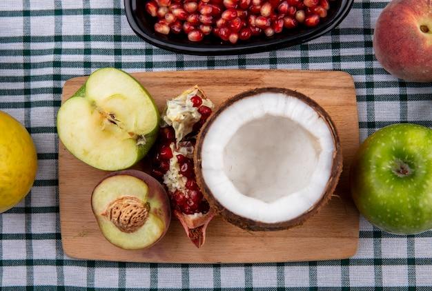 Draufsicht der halben kokosnuss auf einem hölzernen küchenbrett mit halbem apfelhalbpfirsich und granatapfel auf karierter tischtuchoberfläche