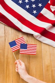 Draufsicht der hand, die amerikanische flaggen hält