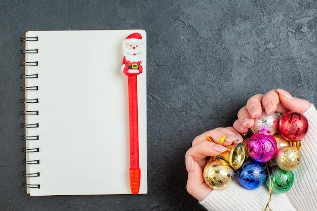Draufsicht der hand, die buntes dekorationszubehör-notizbuch mit stift auf dunklem hintergrund hält