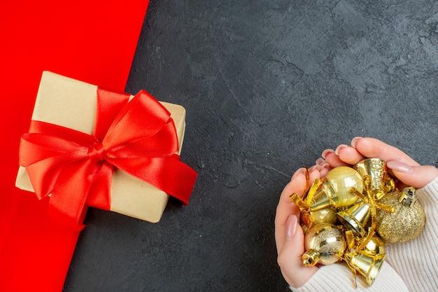 Draufsicht der hand, die buntes dekorationszubehör und schönes geschenk auf rotem handtuch auf dunklem hintergrund hält